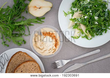 Humus and salad with green arugula plant, pear and cottage cheese isolated. Rustic style. Gray stone background. Close-up. Top view