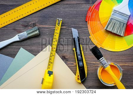 decorating and house renovation tools and accessories on wooden table background top view.