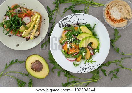Vegetable salad with avocado, arugula, radish, peach and sandwich whith humus. Dietary healthy food. Wooden background. Top view. Close-up