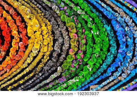 Background consisting of a multitude of multicolored necklaces.