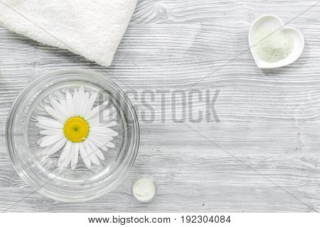 Spa composition on wooden desk with salt, chamomile and towel copyspase top view.