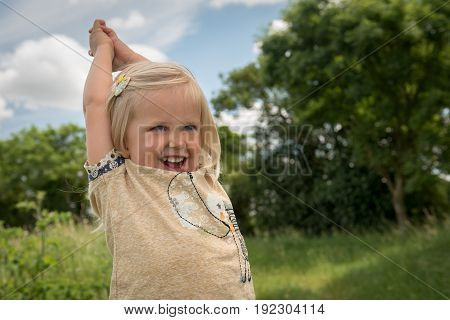 happy little girl with arms raised in a sunny day