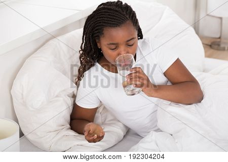 Sick African Girl In Bed Drinking Water While Taking Pill