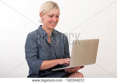 beautiful european mid aged woman working at a laptop - studio shot in front of light background