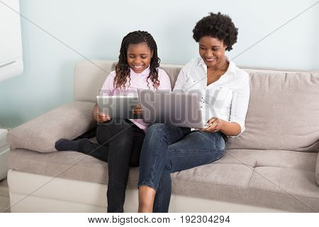 Smiling African Mother And Daughter Sitting On Couch Using Laptop And Digital Tablet