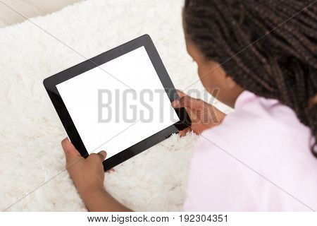 Close-up Of A Girl Lying On Carpet Holding Blank Digital Tablet