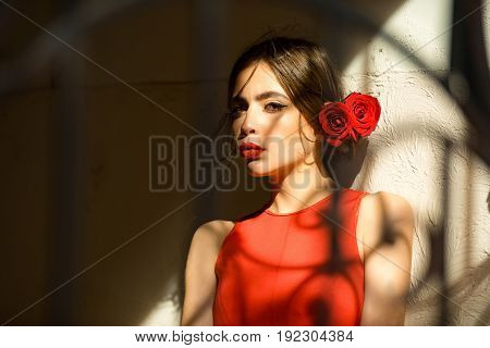 Woman In Red Dress And Roses In Hair At Wall