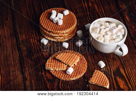 Stroopwafel with Broken One with White Cup of Cocoa with Marshmallow and Waffle Stack. Copy Space on the Left.