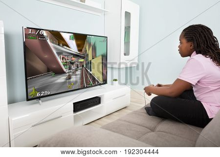 Girl Sitting On Couch Playing Video Game With Joysticks At Home