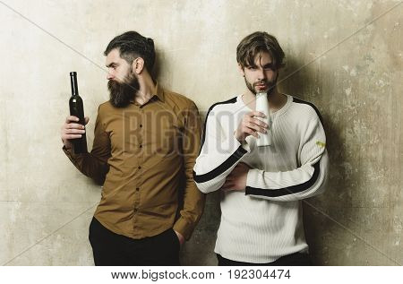 Friends With Drinks Standing On Beige Wall