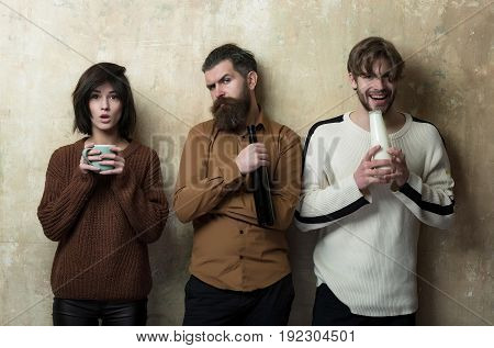 girl standing with cup serious hipster with wine bottle and happy man with milk or yogurt. Group of people or friends with drinks on beige wall. Friendship convive. Healthy or bad habits