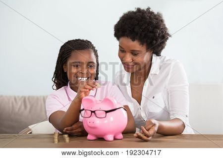 An African Girl Sitting With Her Mother Inserting Coins In Pink Piggy Bank At Home