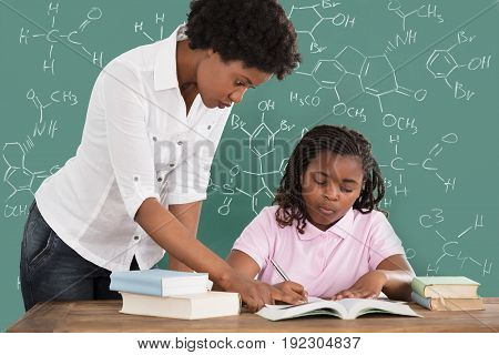 Female Teacher Assisting Student In Studies Against Green Chalkboard