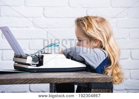 Writer Kid Sitting At Table And Typing Typewriter With Paper