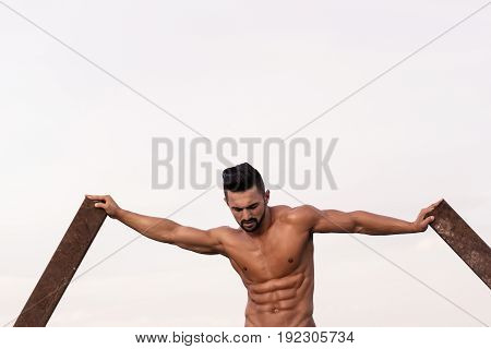workout of guy with muscular wet body and strong torso of bearded bodybuilder athlete in jeans training at rusty iron rod outdoor on landscape background
