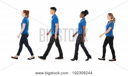 Multiracial Janitors Walking In Row Against White Background