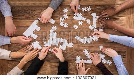 High Angle View Of Businesspeople Hand Solving Jigsaw Puzzle On Wooden Desk