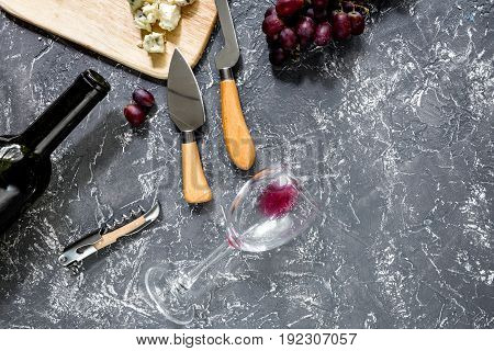 Bottle of red wine with cheese and grape aperitive on grey stone table background copyspace.