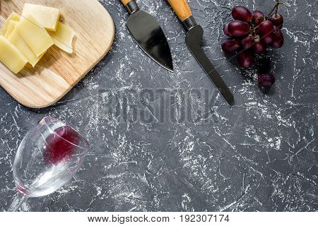 Aperitive parmesan cheese and red grape on grey stone table background copyspace.