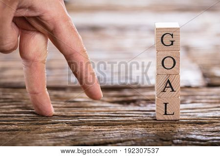 Close-up Of A Person's Finger And Stacked Goal Text On Wooden Block
