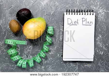 Notebook for diet plan, fruits and measuring tape on grey stone table top view mock up.