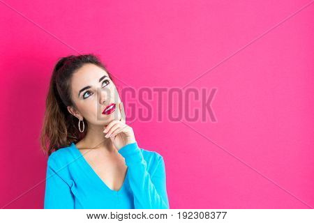 Young woman in a thoughtful pose on a pink background