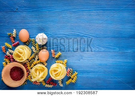 Food ingredients for Italian pasta on blue wooden desk background top view copyspace.