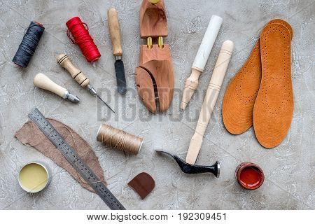 Wooden shoe with shoe tools on grey stone desk background top view.