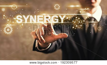 Synergy text with businessman on dark vintage background