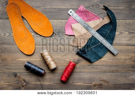 Working place of shoemaker. Skin on brown wooden desk background top view.