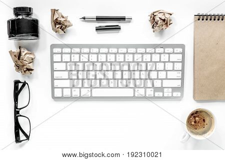 Writer workplace with keyboard, vintage notebook and glasses on white background top view.