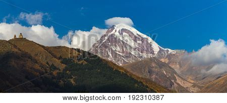 Ancient Trinity Church And A Snow Capped Mountain Of Kazbegi