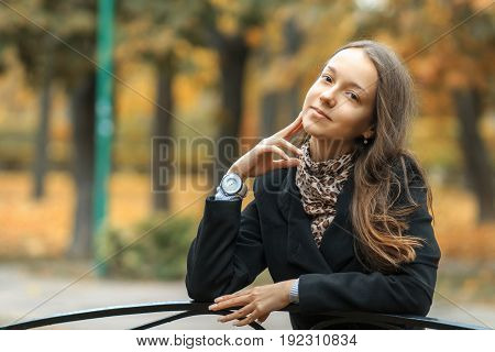 A Young Beautiful White Girl Is Sitting On A Vintage Bench In The Golden Autumn In The City Park. Li