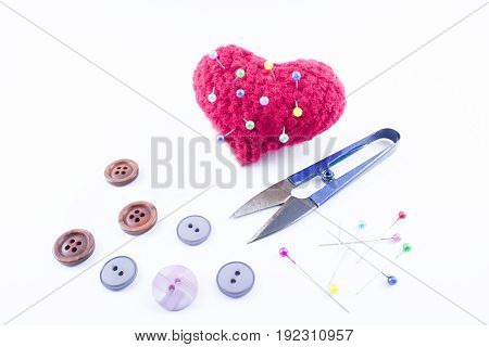Cushion with heart shape with pins of different colors nailed and buttons around on a white background
