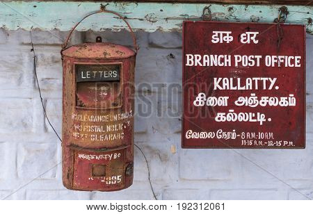 Nilgiri Hills India - October 26 2013: Closeup of rusty mailbox and sign at Kallatty Post Office. White writing on red sign in Tamil and English. Gray and light green wall.