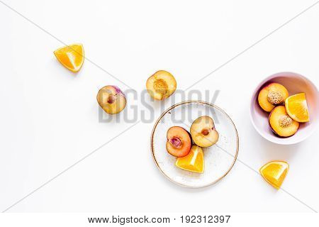 orange and peach summer sweet dessert on plates, white desk background top view mock-up