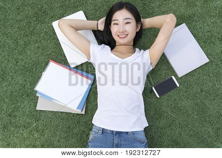 Female College Students Lie On The Playground Lawn Resting Overlooking The Picture