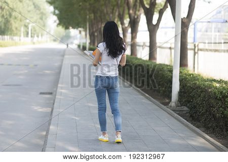 Girl Holding The Books In Campus Back View