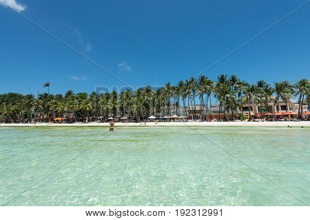 BORACAY, WESTERN VISAYAS, PHILIPPINES - MARCH 27, 2017: Wide angle view from the water to the beach. White beach with many coconut trees.