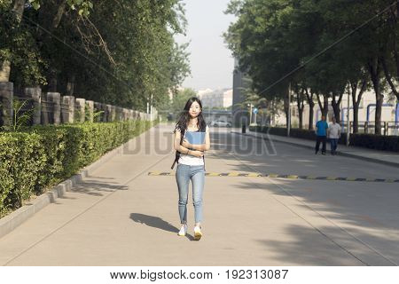 Girl Carrying Bag Walks In Campus Park