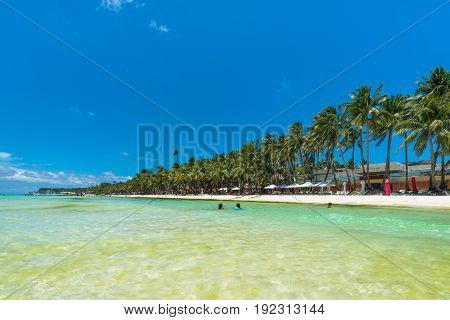 BORACAY, WESTERN VISAYAS, PHILIPPINES - MARCH 27, 2017: The clean and warm water makes the White Beach looks like a swimming pool for children to play.