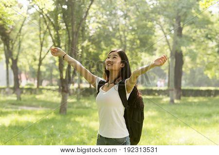 Happy Girl Standing With Her Arms Open Facing The Sun. Sunlight Shone In The Woods.