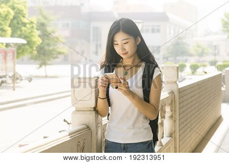Asian Female Students Using Its Ehrs Smartphone In The Campus Corridor