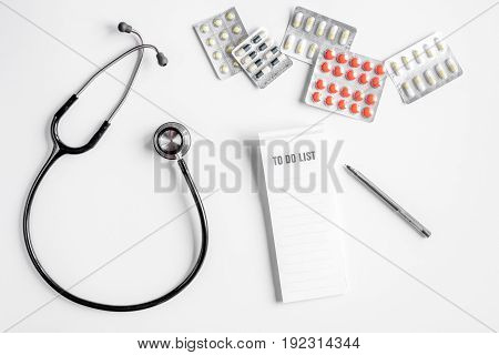 doctor's work desk in hospital with stethoscope and pills on white background top view mockup
