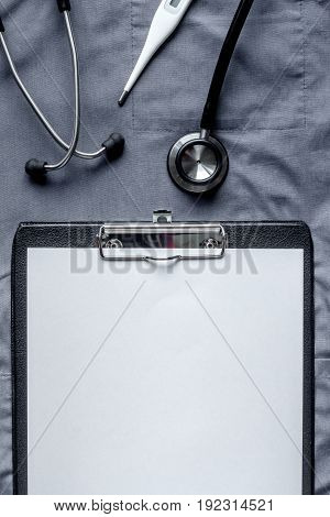 Medical equipment with stethoscope iand notebook n doctor's office in hospital on overall background top view mock-up