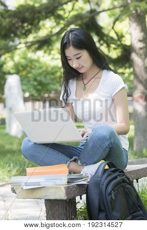 Beautiful Asian College Student With Laptop Sitting On The Campus Bench.