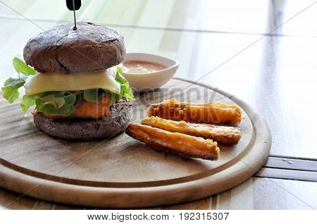 hamburger and french fries on the wooden plate
