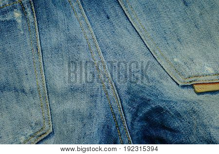 Close-up denim jeans texture. Stitched textured blue denim jeans background. Denim jeans with old torn of fashion jeans design.