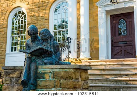 GRANVILLE OH - MAY 15 2017: A statue created by sculptor Diane Powell of a boy and a girl enjoying a book sits outside the original entrance to the Public Library in this charming east-central Ohio village.