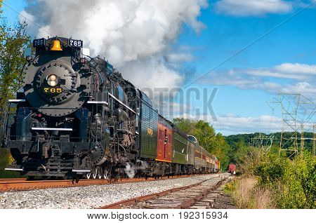 BRECKSVILLE OH USA - SEPTEMBER 14 2013: The historic Nickel Plate 765 steam engine charges down the track as part of the annual Steam in the Valley weekend on the Cuyahoga Valley Scenic Railroad.